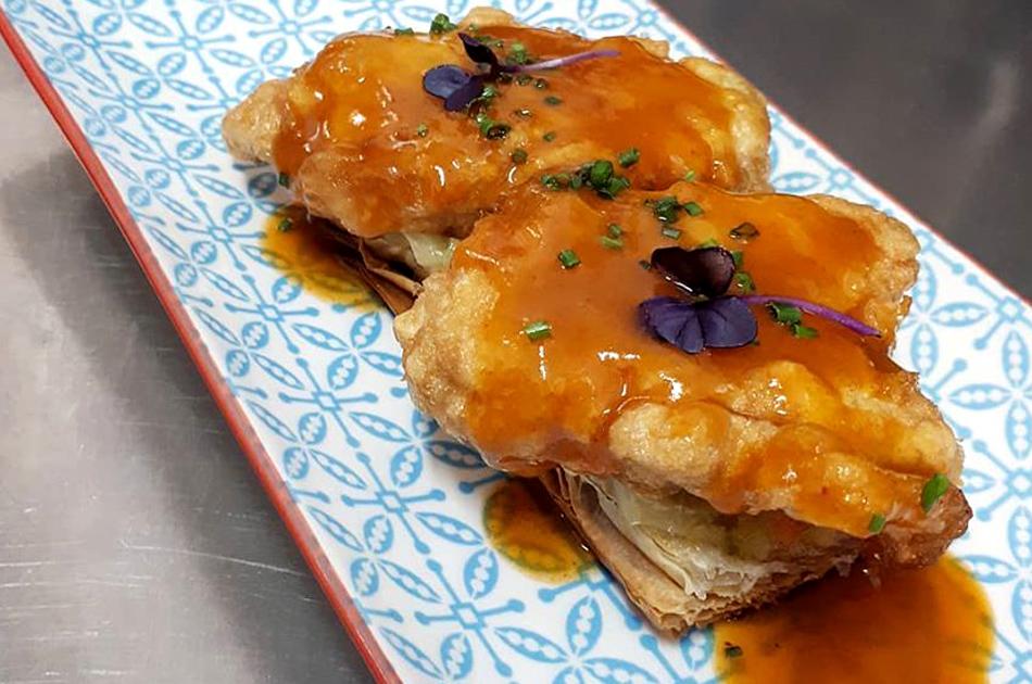 Hojaldre de cocochas de bacalao, verduritas y salsa de callos.